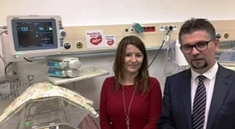 dwie osoby na zdjęciu: kobieta w czerwonej sukience i mężczyzna z brodą w szpitalu na tle sprzętu medycznego