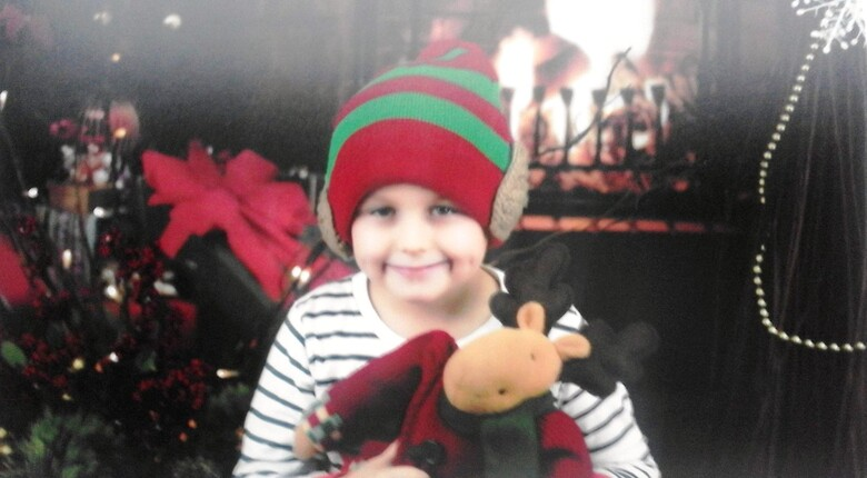 Eryk, podopieczny Fundacji Radia ZET w świątecznej czapce, z pluszowym reniferem